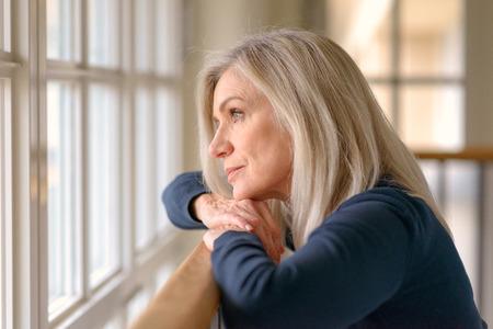Jolie femme blonde debout à rêver alors qu'elle repose ses bras et son menton sur une rampe en bois à regarder par une grande fenêtre