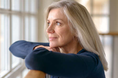 Attraktive Frau mit fröhlichem Gesichtsausdruck, die mit der Hand zum Kinn steht und leise aus einem großen Fenster starrt