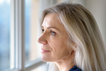 Thoughtful attractive mature blond woman with blue eyes looking out of a window with a quiet smile in a close up profile portrait 写真素材 - 116264943