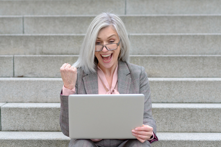 Jubilant businesswoman cheering at good news punching the air with her fist as she sits using a laptop on urban steps