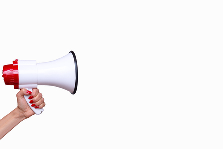 Woman holding a bullhorn or megaphone isolated on a white background with copy space in a conceptual image of vocal communication, protest or public speaking