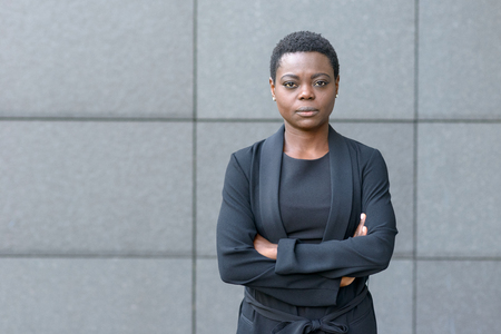 Stern serious young black businesswoman standing with folded arms and a serious expression in front of a grey stone wall