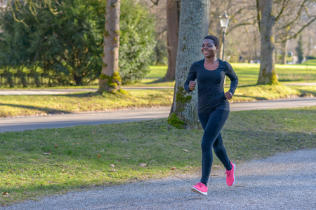 Smiling healthy happy fit young African woman jogging in the park along a tree-lined avenue during her daily exercise workout