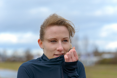 Pretty young woman snuggling into her sports top on a cold winter day as she works out in the countryside in a close up head shot