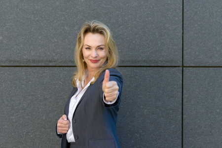 Enthusiastic motivated attractive young woman giving a thumb up gesture of approval and success with a beaming smile Stock fotó