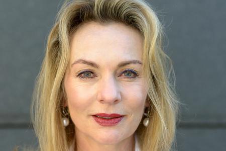 Atractiva mujer rubia de ojos azules con maquillaje en un primer plano disparo a la cabeza contra una pared exterior gris
