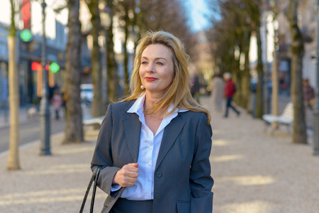 Attractive businesswoman walking confidently down a town street holding her handbag Archivio Fotografico