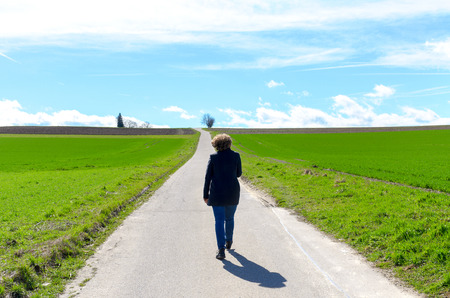 Woman walking away along a country road through lush green fields towards a distant horizon with a sunny blue sky