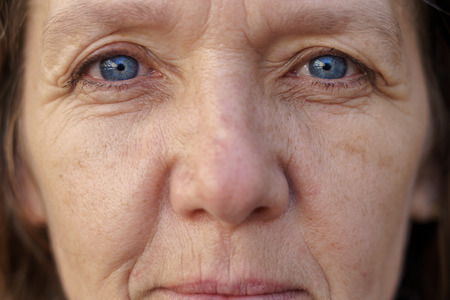 Cropped face of a blue-eyed middle-aged woman with wrinkled skin looking into the lens in a concept of ageing Stok Fotoğraf