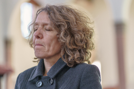 Religious devout woman praying alone in a church with her eyes closed in concentration in a close up portrait
