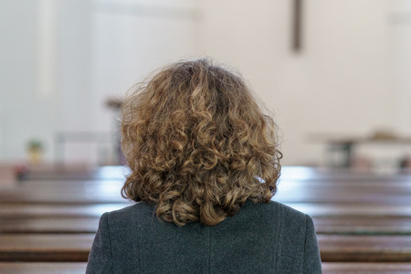 Back view of a Devout religious middle-aged woman praying in a church kneeling alone in a pew