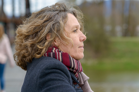 attractive middle-aged woman deep in thought leaning on the railing of a bridge looking away with a serious frown of contemplation
