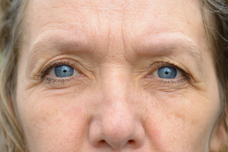 Close-up of pale blue eyes and nose of middle age woman with wrinkled face. Full frame detailed portrait Banco de Imagens