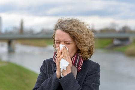 Woman wearing a warm winter coat and scarf blowing her nose on a tissue outdoors on a cold overcast day in a concept of ill health, colds and flu or respiratory allergies 写真素材