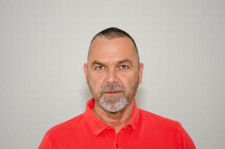 Intensiver Mann mittleren Alters mit einem rätselhaften, ausdruckslosen Ausdruck, der in einer Nahaufnahme von Kopf und Schulter über einen grauen Studiohintergrund in die Kamera starrt