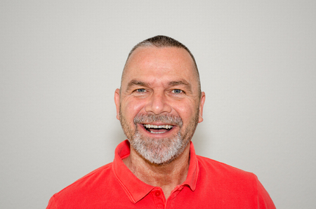 Attractive friendly bearded middle-aged man in a colorful trendy red shirt laughing at the camera with a wide happy smile over a light grey studio background