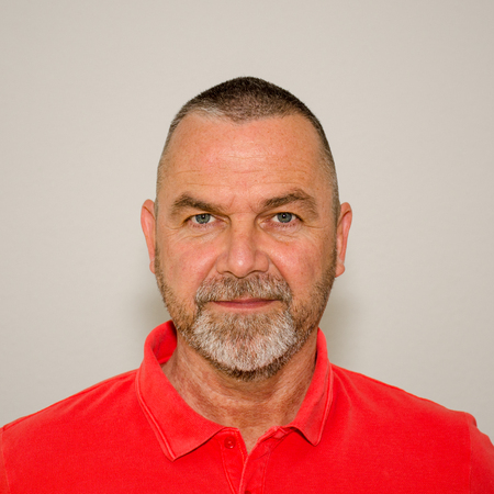 Close up Portrait of an Friendly bearded middle-aged man with short modern haircut wearing a bright red shirt