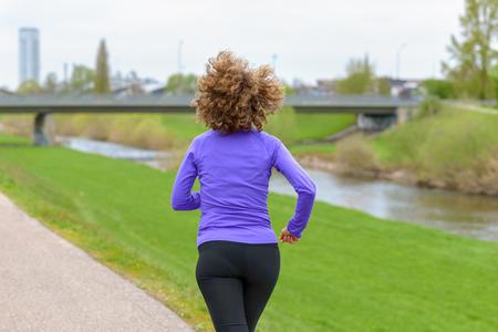 Sportliche Frau in Sportkleidung beim Joggen entlang eines ländlichen Kanals oder Flusses, der von der Kamera wegläuft, wobei ihr Haar in einem Fitness- und gesunden Lebensstilkonzept hinter ihr weht Standard-Bild