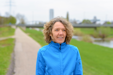 Portrait of middle-aged curly caucasian woman in blue training jacket standing on asphalt walkway outdoors in the park and looking forward. Half-length front portrait with green lawn in background