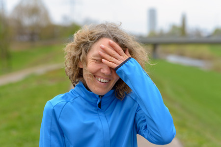 Middle-aged curly woman with curly hair, wearing blue training jacket, smiling, standing and resting with her hand to her forehead after the run. Closeup portrait with green lawn blurred in background