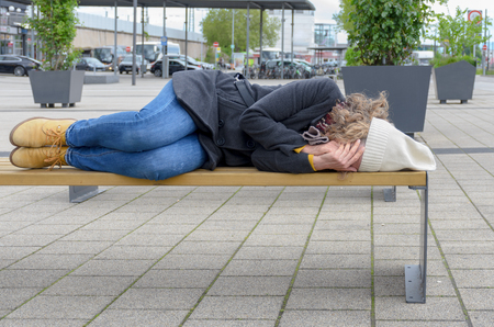 Homeless woman sleeping rough on a bench in a town square covering her face with her hands Stock Photo