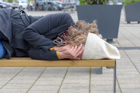 Close up of a homeless woman sleeping rough on a bench in a town square covering her face with her hands