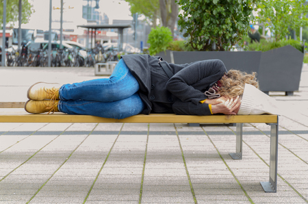 Homeless elderly woman sleeping rough in a park curled up against the cold weather on a rustic wooden bench Stock Photo