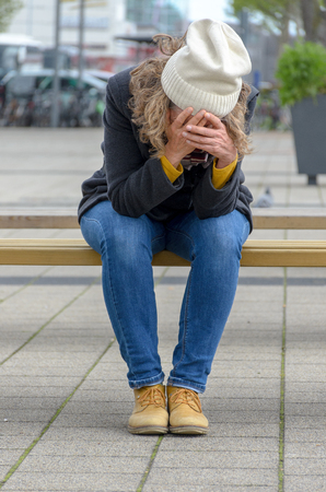 Homeless dejected woman sitting on a city bench wearing jeans and a beanie with her head in her hands in a close up view