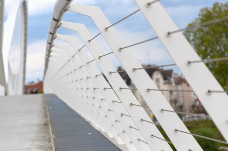 Receding perspective on railings on a bridge with an empty pedestrian walkway in an urban environment