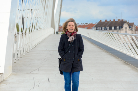Woman crossing a pedestrian bridge with white arched structure and railings approaching the camera with hands in the pockets of her coat