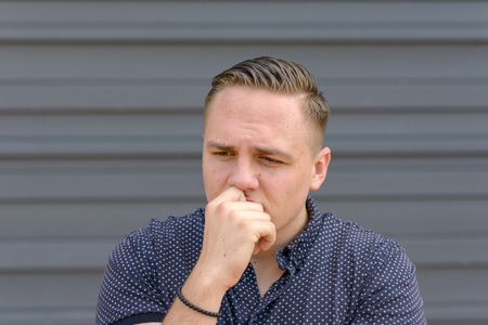 Anxious worried young man frowning as he stands with his hand to his lips and a look of stressed concentration in front of a grey wall Reklamní fotografie