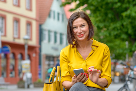 Smiling friendly stylish middle-aged woman in colorful yellow shirt using a mobile in town as she relaxes on a bench in a quiet street Imagens