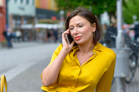 Woman waiting for her call to connect on a mobile phone sitting on a bench in town looking down with a bored expression