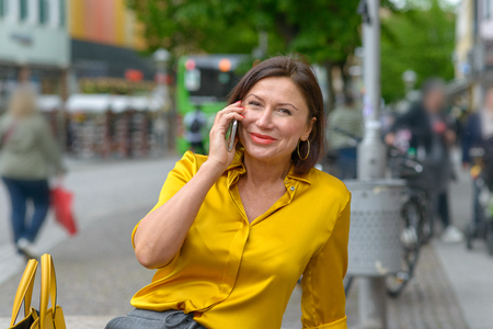 Happy woman chatting on her mobile phone listening to the call with a beaming smile as she sits on a bench in an urban street
