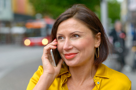 Smiling attractive middle-aged woman talking on her mobile in a street in town in a close up head and shoulders portrait