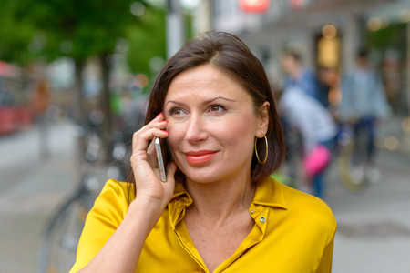 Attractive woman smiling as she listens to a call on her mobile phone while walking through town with a bus passing behind her Zdjęcie Seryjne