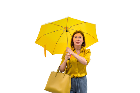 Stylish woman with bright yellow umbrella wearing a matching top with a shocked expression before blank background