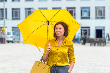 Stylish woman with bright yellow umbrella wearing a matching top walking through town looking up at the weather with a concerned expression