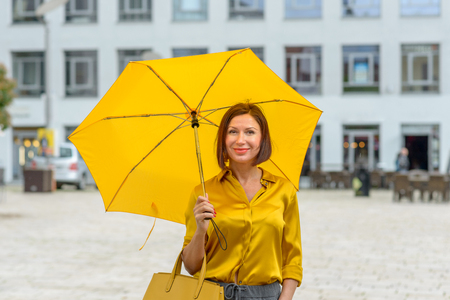 Elegant woman in a fashionable yellow ensemble walking through town and looking to the camera