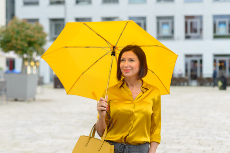 Elegant woman in a fashionable yellow ensemble walking through town with a colorful open yellow umbrella with matching shirt and handbag