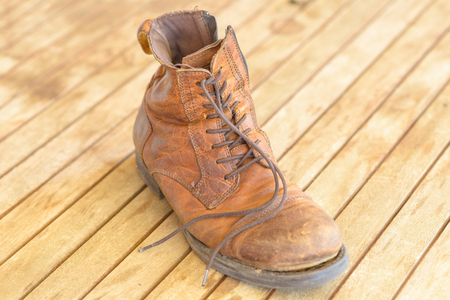 Single old brown well worn hiking boot with scuffed leather and laces on a wooden floor viewed from above