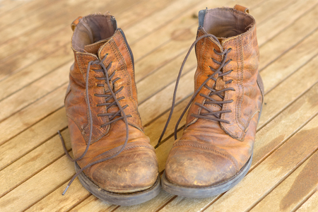 Pair of old worn brown leather hiking boots with laces placed toe to toe on a wooden floor viewed high angle