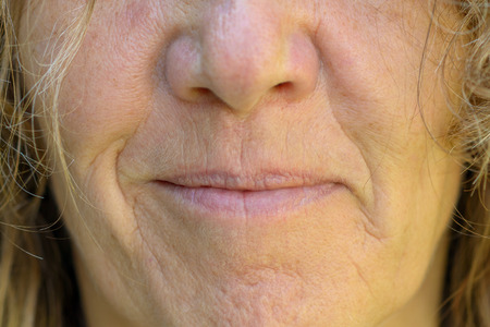Close up on the mouth, nose and lips of a smiling mature woman showing the effects of ageing on the skin