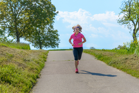 Fit middle-aged woman jogging on a country road through green grassy fields in spring in a concept of a healthy active lifestyle Banco de Imagens - 124815762