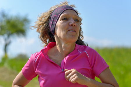 Middle-aged woman jogging in the countryside in a close up portrait against a green field and blue sky in a healthy active lifestyle concept
