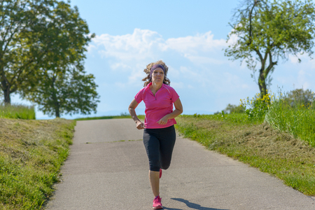 Sporty woman jogging along a country road in spring sunshine in colorful pink sportswear conceptual of an active healthy lifestyle Banco de Imagens - 124815766