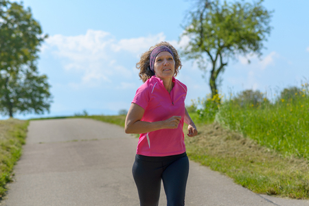 Sporty woman jogging along a country road in spring sunshine in colorful pink sportswear conceptual of an active healthy lifestyle Banco de Imagens