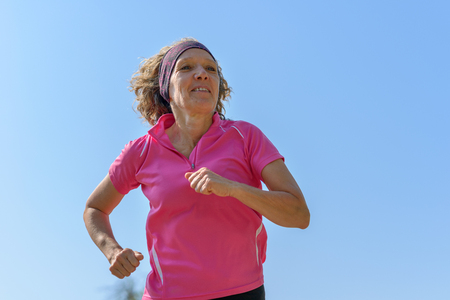 Fit middle-aged woman jogging in spring sunshine viewed close up low angle as she passes the camera against a sunny blue sky