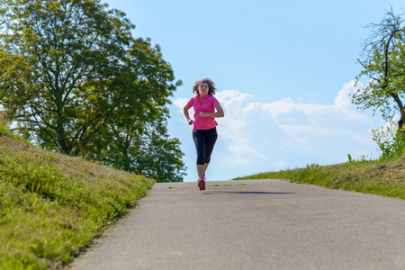 Mature athletic woman jogging on a rural road in spring sunshine approaching the camera against a sunny blue sky with foreground copy space Banco de Imagens