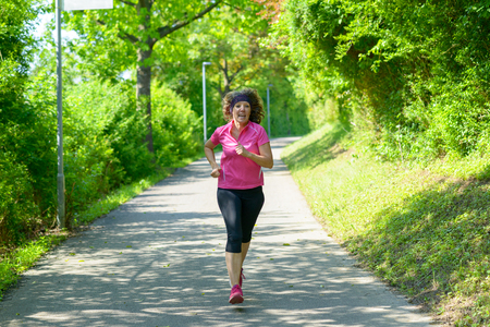 Fit middle-aged woman out jogging in spring approaching the camera along a winding road through leafy green trees conceptual of a healthy active lifestyle Banco de Imagens